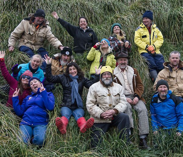 A team of seven men and seven women sit in the green tussock