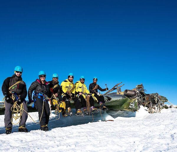 Expeditioners sitting on wing of aircraft remains
