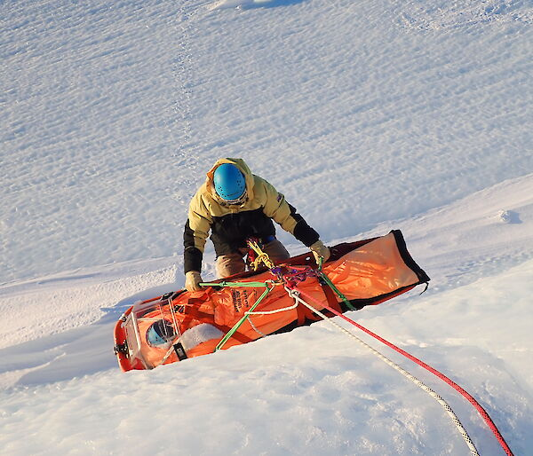 Mawson Search and Rescue team member carrying out a stretcher haul at 'Endwave' in the Framnes Mountains.