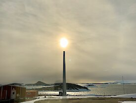 The sun above, and halo around, the disused turbine tower, appearing almost as a candle — Mawson.