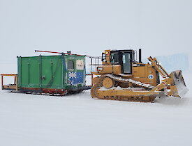 Rumdoodle Hut being towed by a D-15 Dozer down the GWAM ice road to Mawson Station.