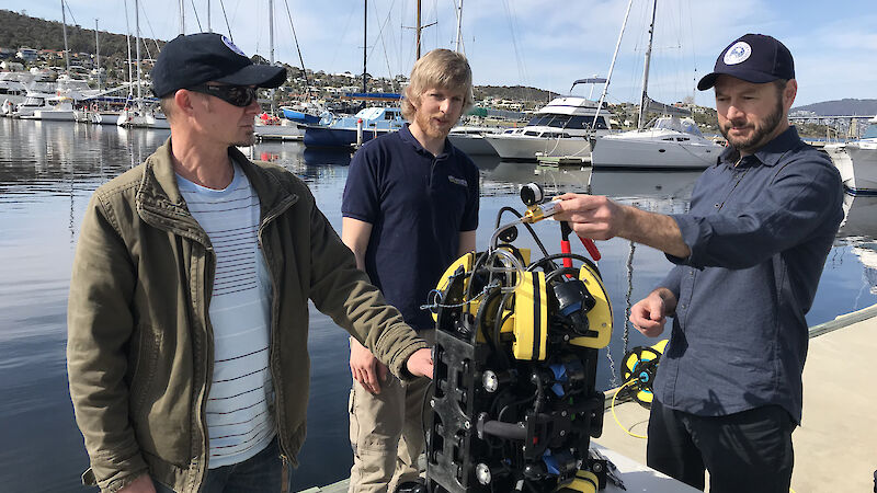 Dr Jonny Stark (left), SOSub Director Kelsey Treloar, and Dr Glenn Johnstone, with the ROV, at a wharf in Hobart.