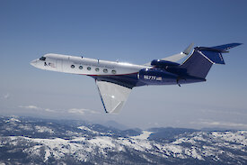 A Gulfstream V aircraft flying over mountains.