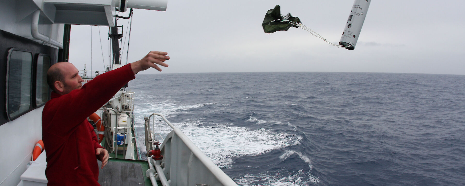 Acoustician Dr Brian Miller throws a sonobuoy into the ocean from the side of the ship
