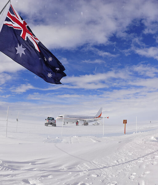 Australian flag flying with aircraft in distance.