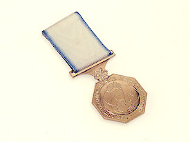 A bronze medal depicting a map of Antarctica and the words 'For Outstanding Service in the Antarctic'