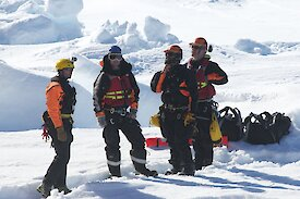 Rescue team preparing landing spot on the ice for the helicopter