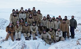 Large group of expeditioners posing for photo in tradeswear.