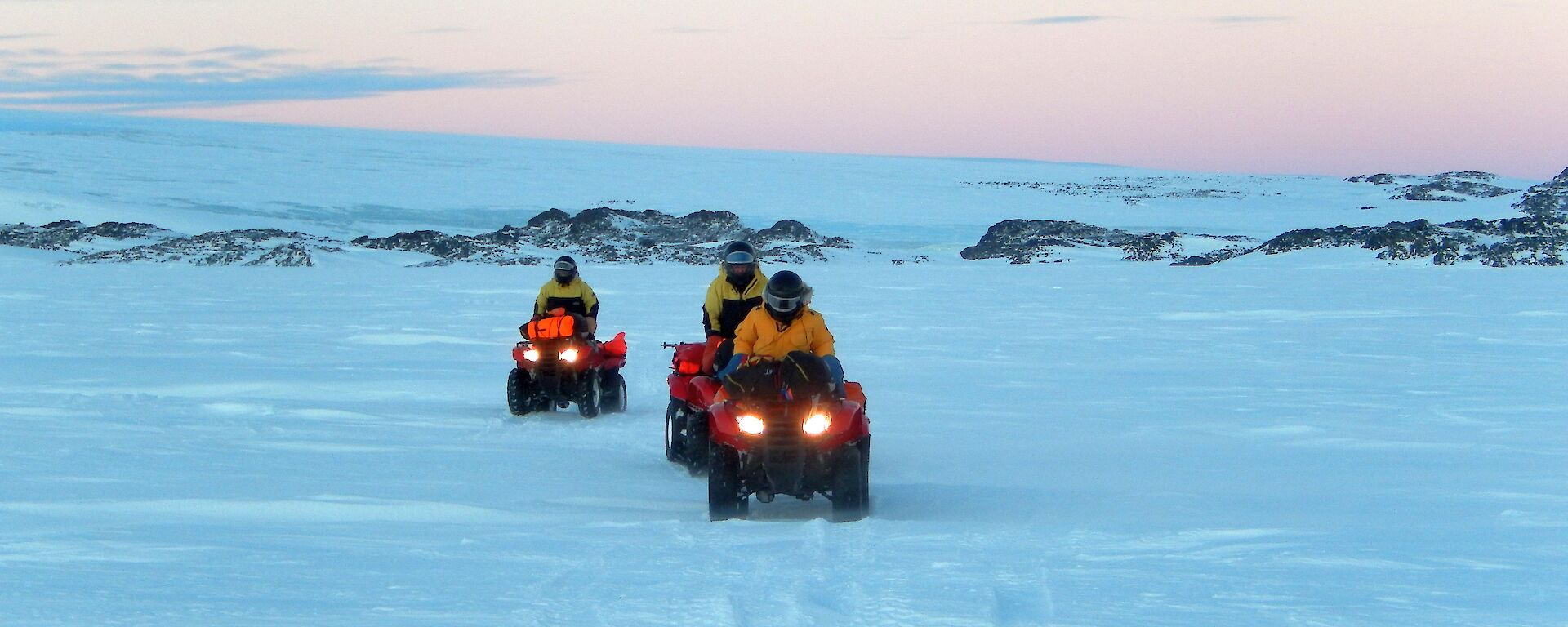Three expeditioners riding quad bikes on the sea ice