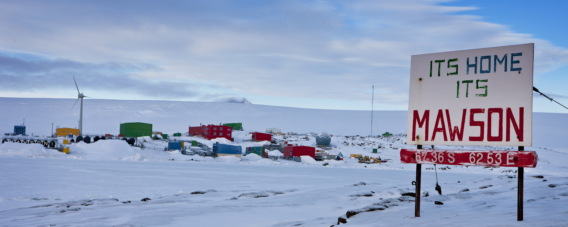 "Mawson station from West Arm after snowfall, showing station sign ""Its Home its Mawson"" plus a iced over Horseshoe Harbour"