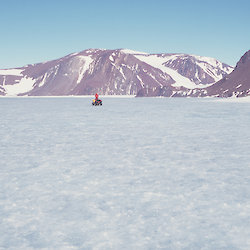 A broad expanse of ice ringed by mountains with a person on a quad bike in the middle of the lake.