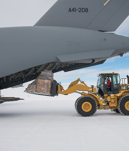 Large yellow tractor remove cargo at rear of heavy lift cargo aircraft.