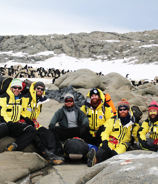 A group of expeditioners wearing yellow with penguins in background.