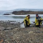 two scientists on rocky shore beside lake
