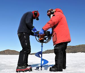 two men with large auger on sea ice