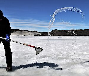 man flicks water out of ice hole with sieve