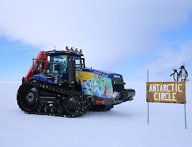 Tractor beside the Antarctic Circle sign