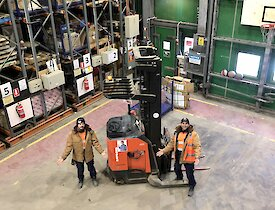 Two men standing next to a forklift in a warehouse