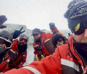 A team of masked expeditioners in a small boat pose for a photo.