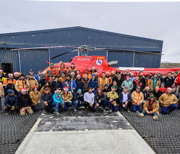 The Davis cohort pose in front of a red helicopter for a snowy, Christmas themed group photo.