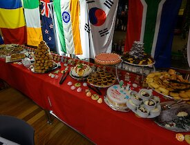 A long table draped in red cloth is covered in various, delicious looking desserts on Christmas Day dinner. Flags from various nations adorn the wall behind.
