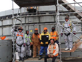 A group of seven workers stand in front of a grey water tank that they have been cleaning.