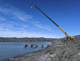 A large mobile crane holds a pontoon in place as it floats on the grey tarn.