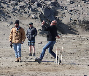 A man bowls a ball down the cricket pitch while two other men look on from the field
