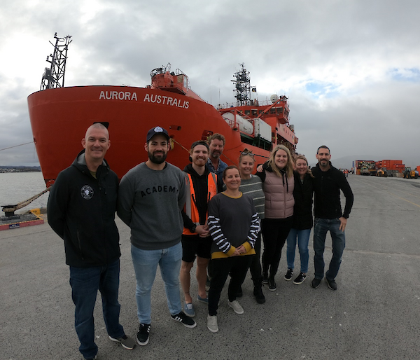 The hydrography team stop for a photo in front of the Aurora Australis ship in Hobart