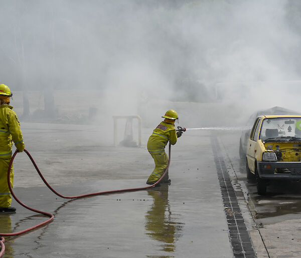 Chef Donna dressed in firefighting attire extinguishes a blazing car at fire training