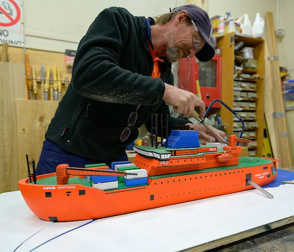 Carpenter makes a saw cut on his scale workshop model Aurora Australis ship