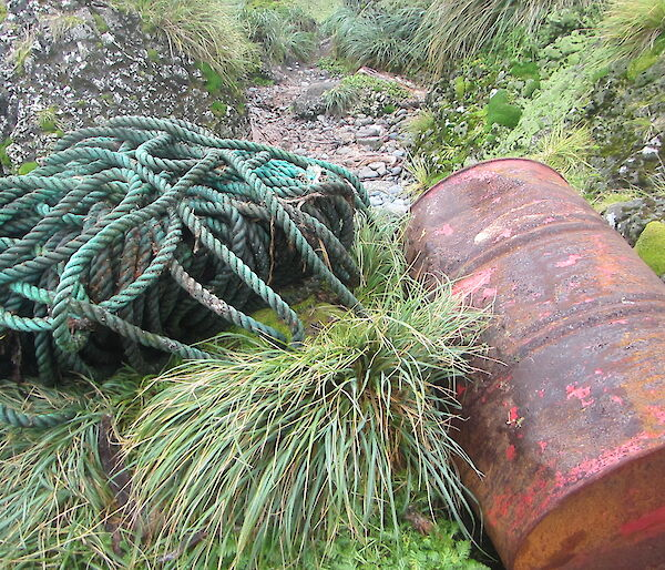 long, rolled up rope and rusty oil drum on the shore