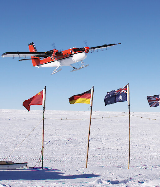 A Twin Otter flies over flags, planted in the ice, of countries participating in a geophysical research project.