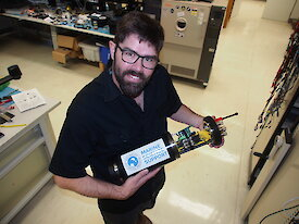 Mark Milnes holds the test device for Nuyina's fibre optic and electrical cables.
