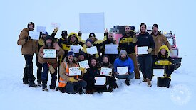 A group of expeditioners in the snow, holding up hand-written Happy Mother's Day signs