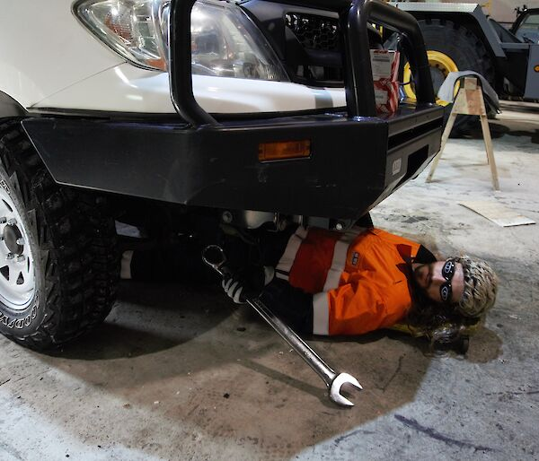 Field training officer in the vehicle workshop, lying under a vehicle