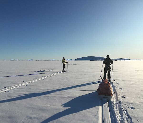 Two expeditioners ski towards Anchorage Island across snow covered sea ice into the low sun and blue sky