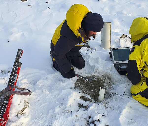 Two expeditioners sit on the snowy ground while taking measurements from a soil probe