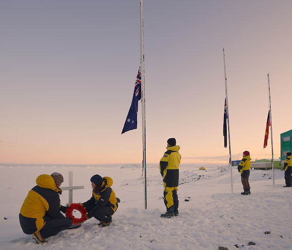 Expeditioners laying wreath at cross. Three flags half mast