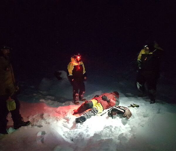 "Jason the ""casualty"" lies on the snow covered ground in the dark surrounded by rescuers"