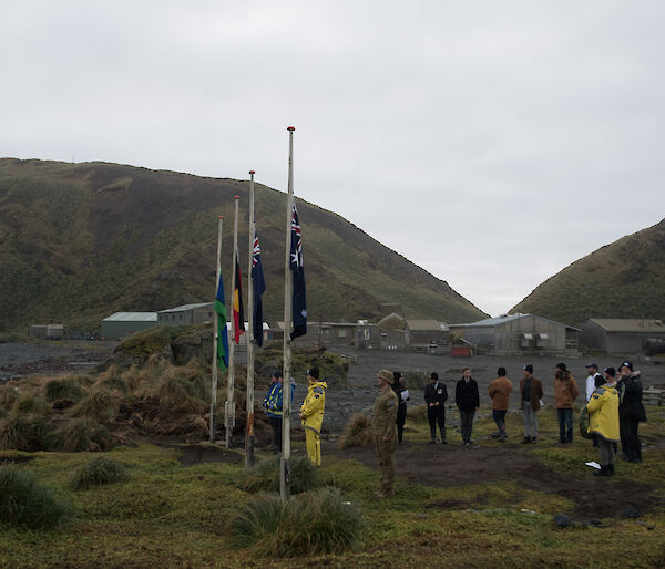 Group of expeditioners gathered around flag poles