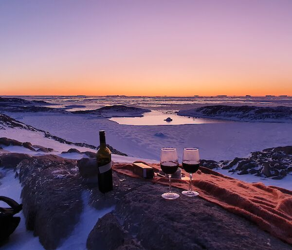 A bottle of wine and two glasses in front of a colourful sunset over the ice.