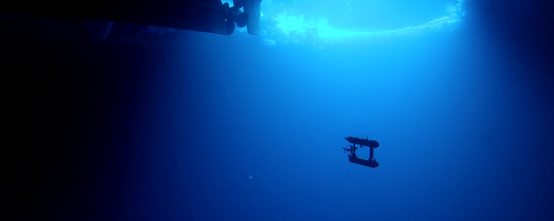 AUV underwater with ship visible above.