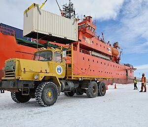 A Mack truck on the sea ice beside the icebreaker Aurora Australis, with a crane lowering a shipping container onto its flat deck.