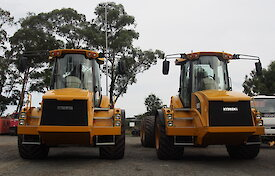 Two yellow tip trucks side by side.