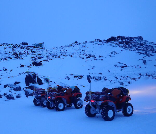 four quad bikes in front of a landscape of snow and rocks
