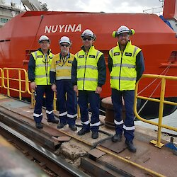 Captain Scott Laughlin and three other Serco team members in front of the Nuyina.