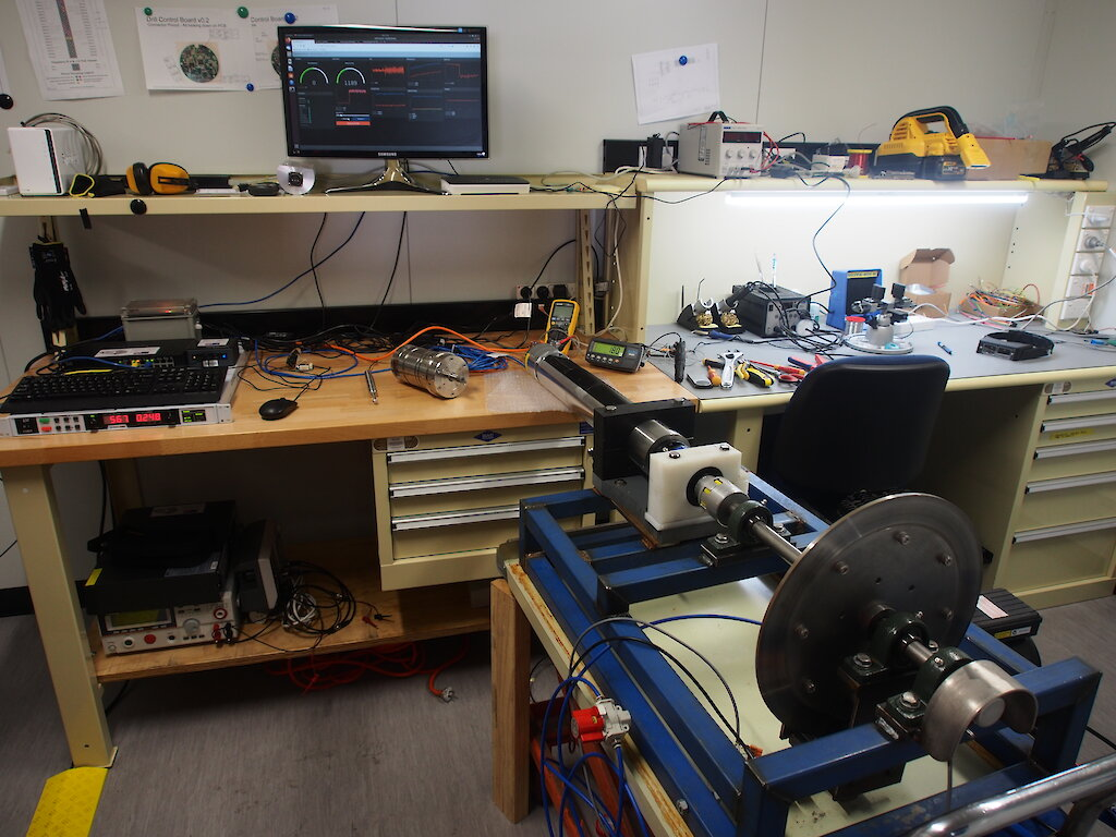 A cyclinder containing drill electronics attached to a brake pad to simulate drilling into ice, on a laboratory bench.