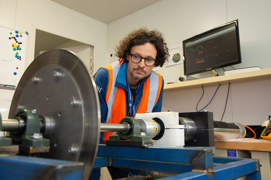 An engineer looks at the ice core drill rig.