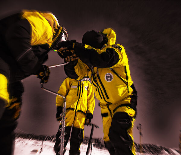 Three people wearing yellow jackets holding a piece of equipment with a dark sky behind them.